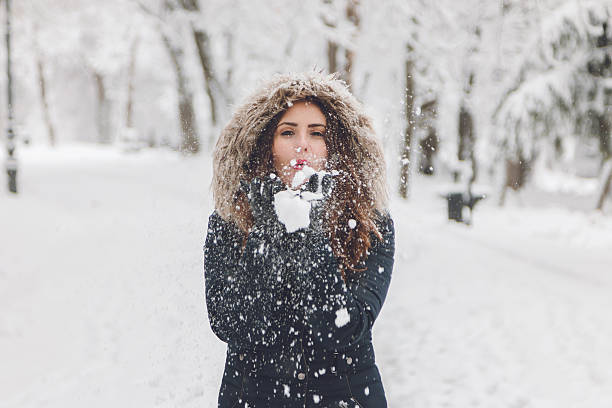 Winter portrait of a lady blowing a handful of snow – Foto