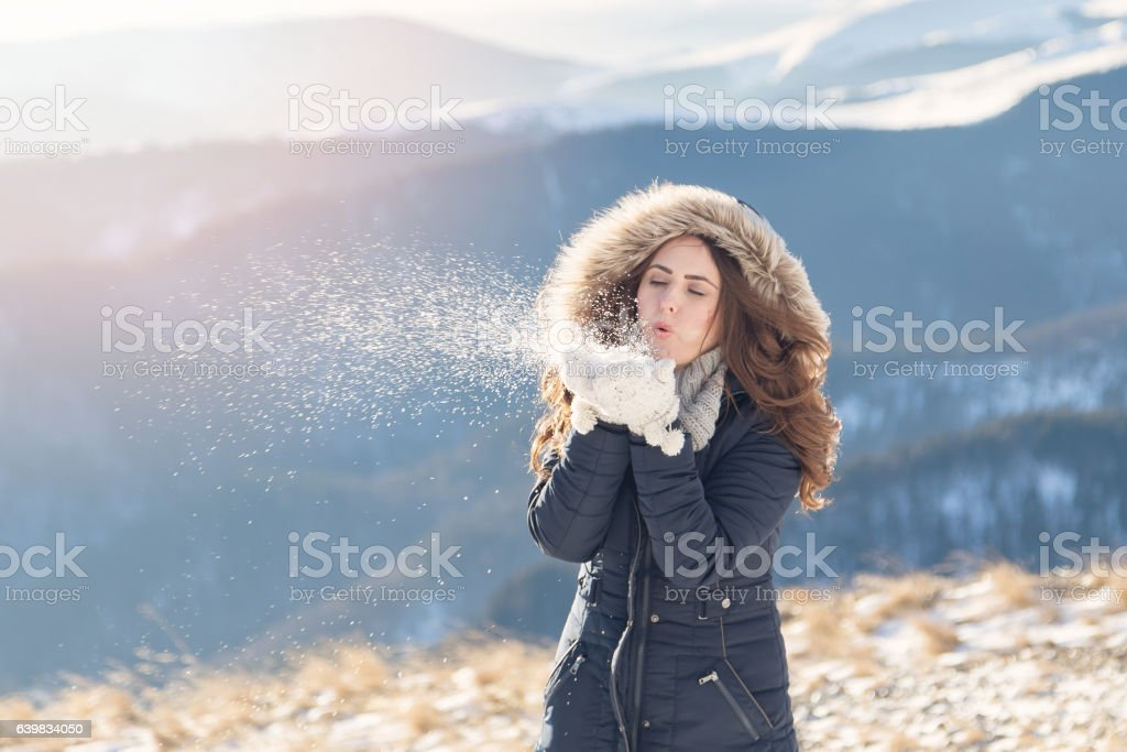 Winter portrait of a lady blowing a handful of snow stock photo