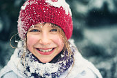 Winter portrait of a beautiful little girl laughing and having a lot of fun in snow. The girl aged 8 and her scarf, face and cap are snow covered. Some of the snow have melted on her cheeks.