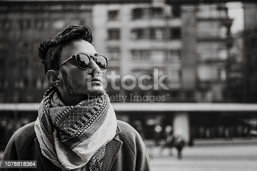 Portrait of a gen z man in the city. Winter scene, black and white image.