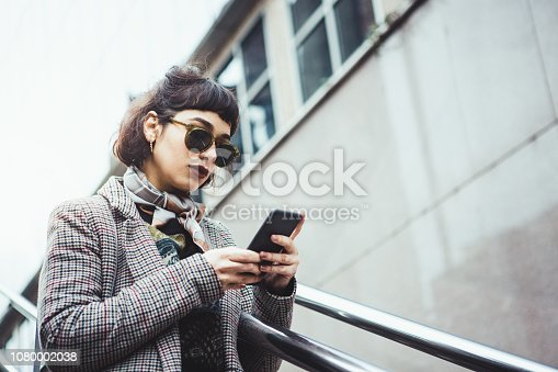 portrait of a gen z woman in the city using mobile phone