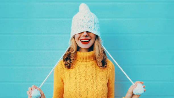 Winter portrait of cheerful woman pulls a hat over her eyes wearing yellow knitted sweater and white hat with pom pom on blue background stock photo