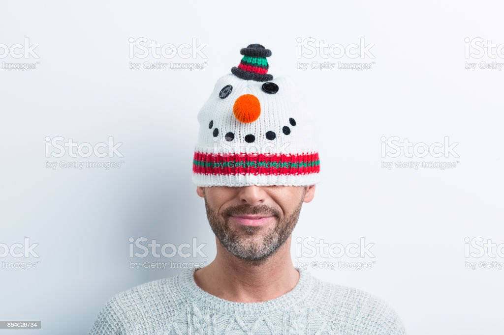 Winter portrait of happy man wearing snowman cap Funny winter portrait of happy man wearing snowman cap. Mid adult man in winter outfit. 35-39 Years Stock Photo