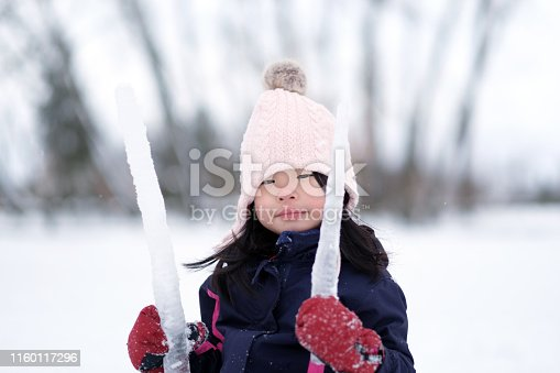 istock Winter portrait of little child girl wearing knitted hat 1160117296