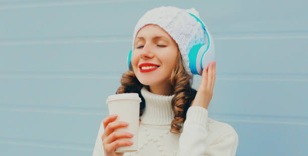 Winter portrait of smiling woman listening to music in headphones with coffee cup wearing a white hat, knitted sweater over blue background stock photo