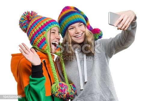 istock Winter portrait of two happy beautiful teenage girlfriends in knitted hats having fun with mobile phone, taking selfie, isolated on white background. People, youth and friendship concept 1042031060
