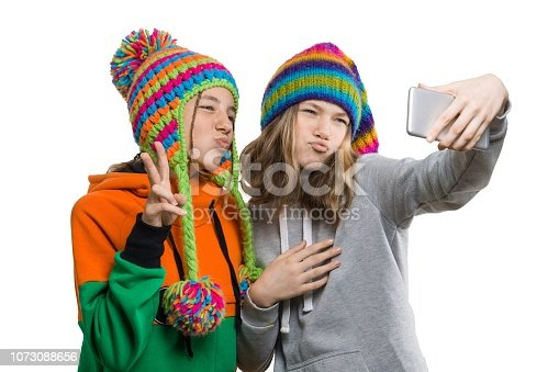 istock Winter portrait of two happy beautiful teenage girlfriends in knitted hats having fun with mobile phone, taking selfie, isolated on white background. People, youth and friendship concept 1073088656
