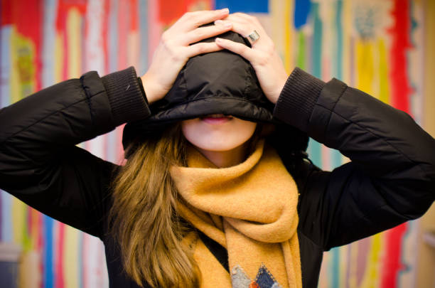 Winter portrait of young woman hiding face stock photo