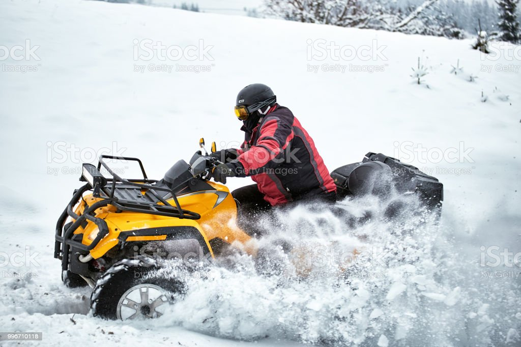 Winter race on an ATV on snow in the forest. stock photo