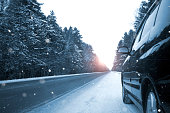 Winter road among coniferous forest, black car, it is snowing