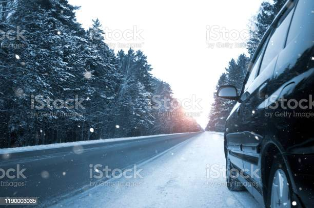 Photo of Winter road among coniferous forest, black car, it is snowing