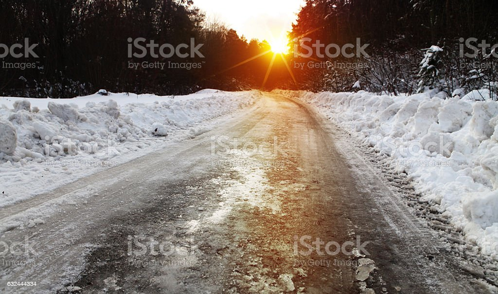 winter road and forest at sunset - foto de stock