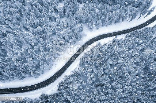 Black asphalt road leading through snowcapped winter forest. Aerial view. Snow is fallling from the clouds.