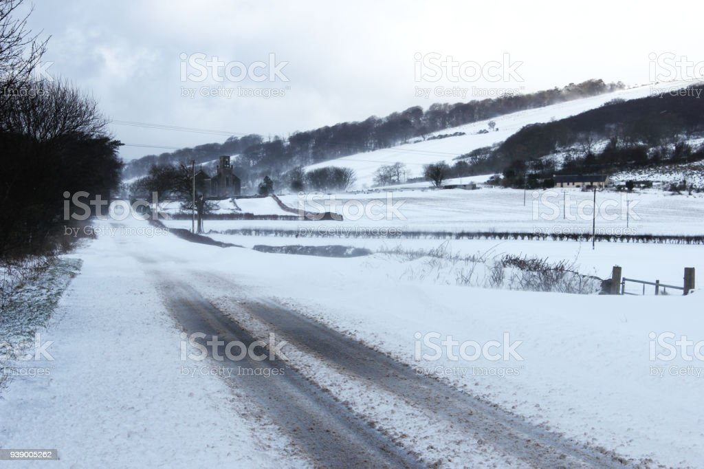 Road through snow covered landscape on the Isle of Bute, Scotland.