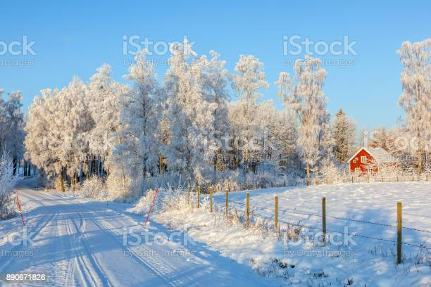Photo of Winter road with a red cottage in rural landscape