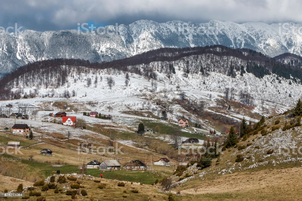 Winter rural landscape with traditional farm houses near Piatra Craiului massif in Sirnea village, Brasov county. stock photo