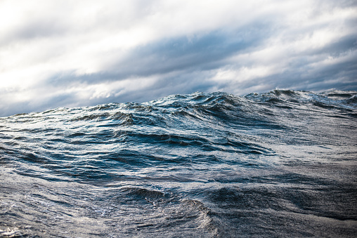 Winter sailing. Cold blue sea at sunset. waves and clouds, Norway