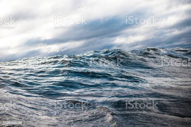 Photo of Winter sailing. Cold blue sea at sunset. waves and clouds, Norway