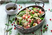 Winter Salad with Quinoa, Avocado, Blood Orange, Pomegranate, Bulgur, Hazelnuts on blue Background
