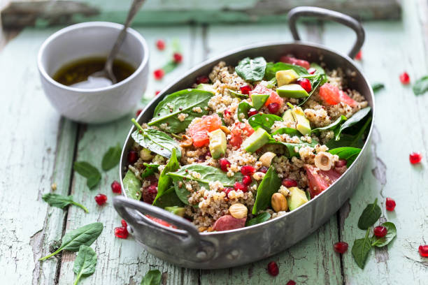 winter salad with quinoa, avocado, blood orange, pomegranate, bulgur, hazelnuts - quinoa stock photos and pictures