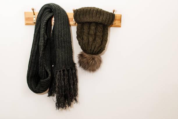 winter schal und wolle cap mit einem pelzigen kugel und hängt an einem kleiderständer auf weißem hintergrund - garderobenhaken stock-fotos und bilder
