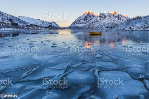 Photo of Winter scene of boat in partially frozen fjord and snowy mountain landscape