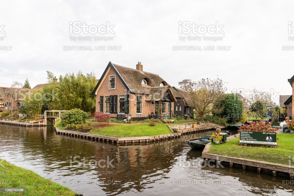 Winter scene of narrow canals and residential buildings with boats and signs in the famous village Giethoorn Netherlands. stock photo