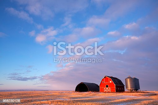 Low light hitting the barn, light is just skimming across the field. Saskatchewan , Canada. Image taken from a tripod.