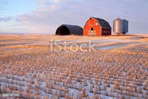 Low light hitting the barn, light is just skimming across the field. Saskatchewan , Canada. Image taken from a tripod.