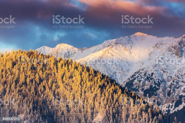Photo of Winter scenery in the mountains, with snow covered peaks and setting moon