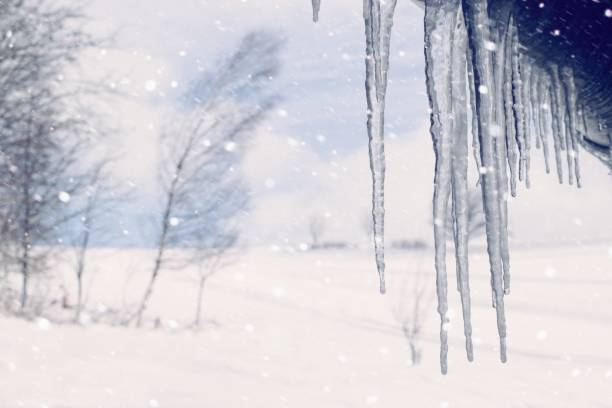 Winter scenery with hanging icicles and white landscape on the background stock photo