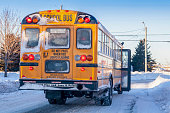 A typical yellow school bus stopped to pick up passengers on an extremly  cold winter day.