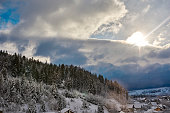 horizontal shot of day in winter time, snow covering forest and village.