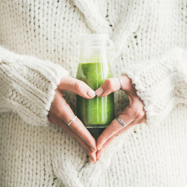 Winter seasonal smoothie drink detox in woman's hands, square crop Winter seasonal smoothie drink detox. Female in sweater holding bottle of green smoothie or juice making heart shape with her hands, square crop. Clean eating, weight loss, healthy dieting food concept detox stock pictures, royalty-free photos & images