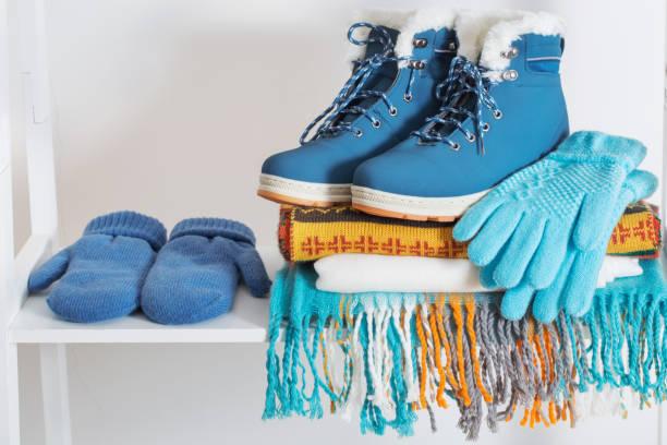 winterschuhe, handschuhe und schal auf weißen holzregal - damenschuhe k stock-fotos und bilder