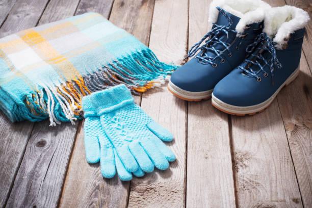winterschuhe, handschuhe, schals auf alten hölzernen hintergrund - damenschuhe k stock-fotos und bilder