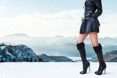 Winter shoes.Woman with black leather coat and boots in mountain.