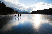 Three women enjoy a winter ice skate on Johnson Lake in Banff National Park, Alberta, Canada. Two of the women skate with ice hockey sticks.