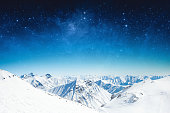 fantastic winter sky stars and the snow-capped mountains. Elements of this image furnished by NASA