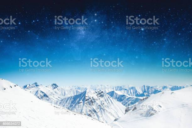 Photo of winter sky stars and the snow-capped mountains