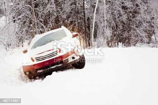 Winter snow accident featuring a car in a ditch on a snow-covered country road with the lights on. Falling snow visible, lots of snow on the car.