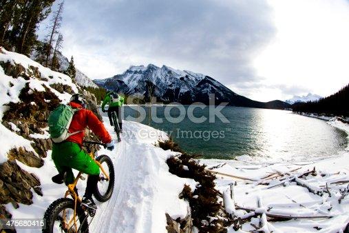A man and woman enjoy a winter fat bike ride along Lake Minnewanka in Banff National Park, Alberta, Canada.