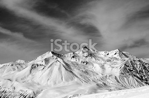 Winter snow mountains in windy day. Caucasus Mountains, Georgia, region Gudauri. Black and white toned landscape.