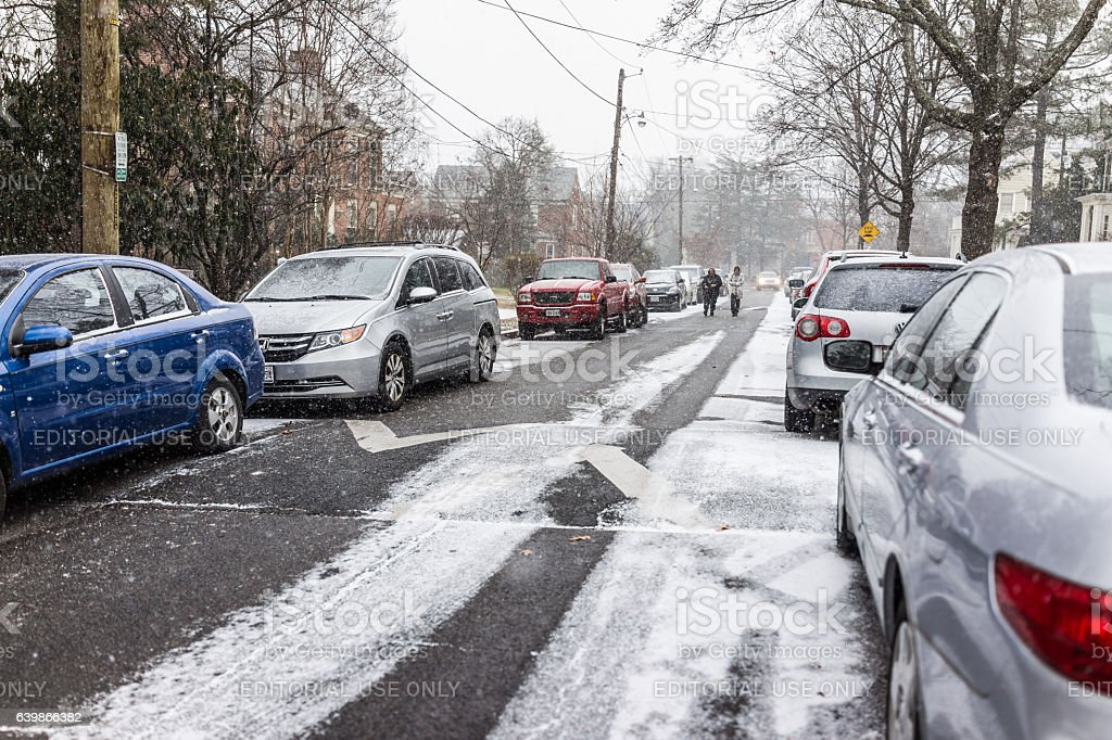 Winter snow storm on street with parked cars stock photo