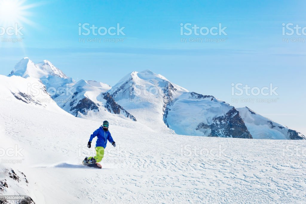 Male snowboarder on the slope with mountain peaks on background