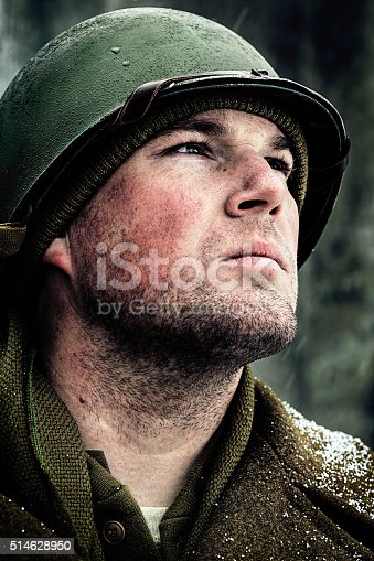 Pensive, young World War 2 soldier with winter helmet looking toward the future.