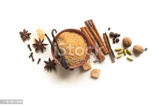 Winter Spices and Brown Sugar isolated on white background, top view, copy space. Mulled wine or Christmas seasonal baking ingredients - aroma spices.