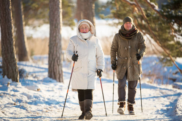 Winter sport in Finland - nordic walking Winter sport in Finland - nordic walking. Senior woman and man hiking in cold forest. Active people outdoors. Scenic peaceful Finnish landscape. nordic walking stock pictures, royalty-free photos & images