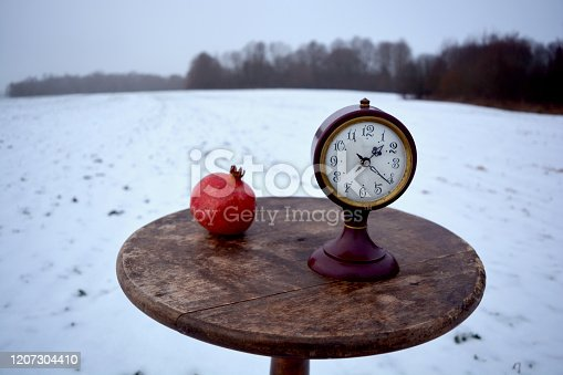 Winter still life with pomegranate and ancient clock on circle wooden retro table on snowy field