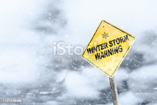 Winter storm season with snowflake symbol sign against a snowy background and copy space. Snow splattered and angled sign adds to the drama.